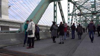 Des participants à des visites guidées marchent sous la structure d'acier du pont Champlain